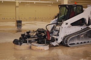Bobcat grinding concrete with 3 grinding heads.