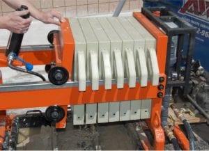 Cylinder tilted back, compression plate released for removing individual cake plates.